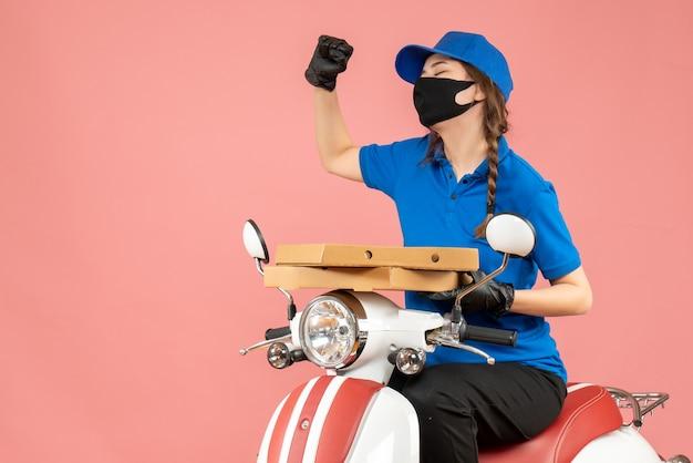 Bovenaanzicht van een jonge, gelukkige emotionele vrouwelijke koerier met een medisch masker en handschoenen die op een scooter zitten en bestellingen afleveren op pastel perzik