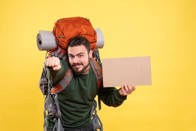 Bovenaanzicht van een jonge glimlachende en zelfverzekerde reizende man met rugzak die een laken vasthoudt zonder op geel te schrijven writing