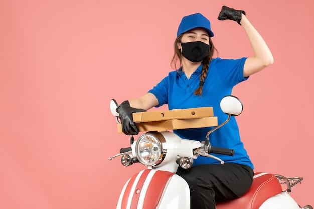 Bovenaanzicht van een jonge glimlachende, gelukkige vrouwelijke koerier met een medisch masker en handschoenen die op een scooter zit en bestellingen aflevert op pastel perzik