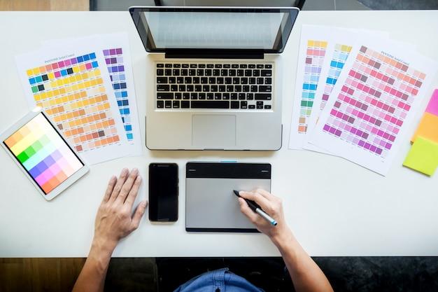 Bovenaanzicht van een jonge grafische ontwerper die op een desktopcomputer werkt en wat kleurstalen gebruikt, bovenaanzicht.