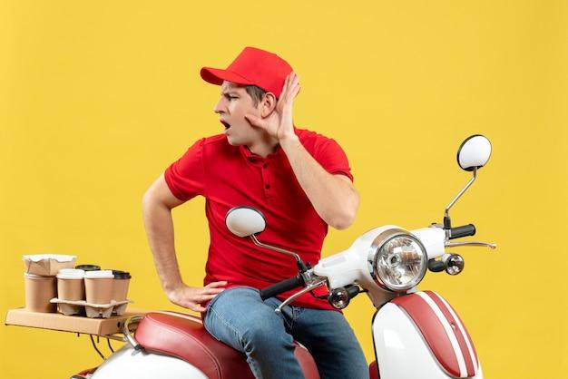 Bovenaanzicht van een jonge kerel die een rode blouse en een hoed draagt en bestellingen aflevert, luisterend naar de laatste roddelen op gele achtergrond