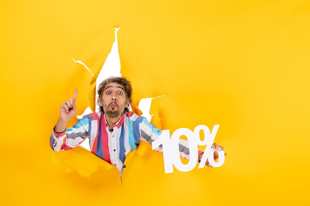 Bovenaanzicht van een jonge man die tien procent toont en omhoog wijst in een gescheurd gat in geel papier