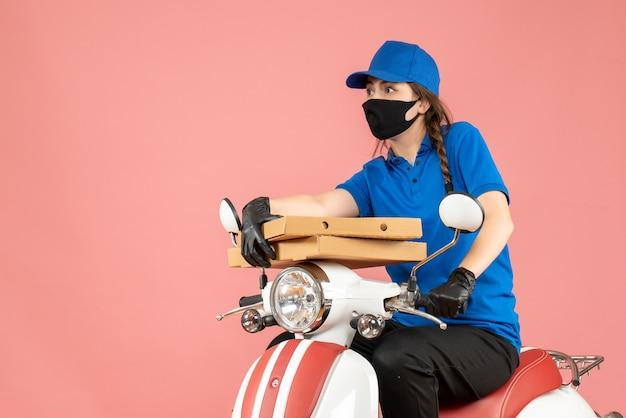 Bovenaanzicht van een jonge, nieuwsgierige, emotionele vrouwelijke koerier met een medisch masker en handschoenen die op een scooter zit en bestellingen aflevert op pastel perzik
