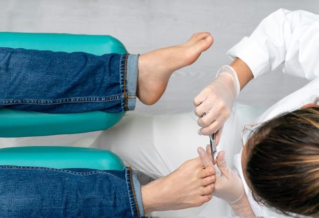 Bovenaanzicht van een jonge pedicure die pedicure in haar podologie kliniek doet