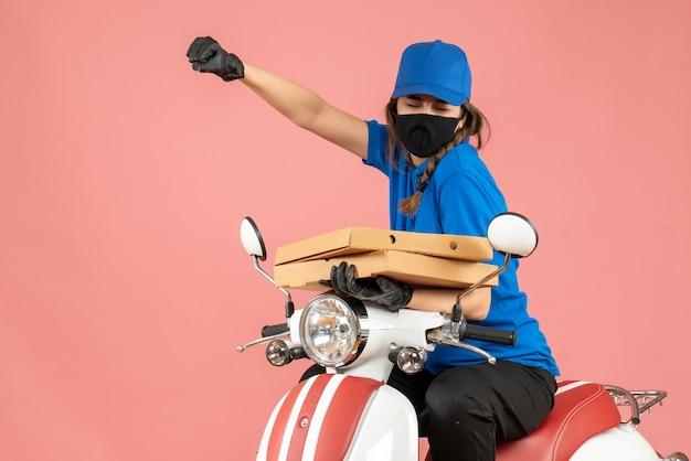 Bovenaanzicht van een jonge trotse emotionele vrouwelijke koerier met een medisch masker en handschoenen die op een scooter zitten en bestellingen op pastel perzik afleveren