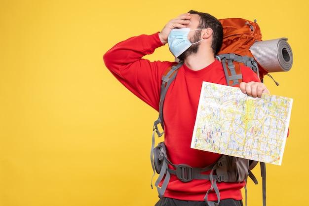 Bovenaanzicht van een jonge uitgeputte reiziger die een medisch masker draagt met een rugzak met een kaart op geel
