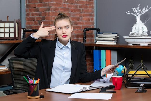 Bovenaanzicht van een jonge vrouw die aan een tafel zit en een document vasthoudt en een pistoolgebaar maakt op kantoor