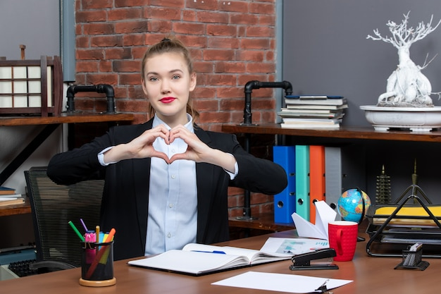 Bovenaanzicht van een jonge vrouw die aan een tafel zit en een hartgebaar maakt op kantoor