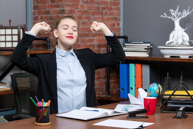 Bovenaanzicht van een jonge vrouw die aan een tafel zit en het document vasthoudt terwijl ze droomt over iets op kantoor