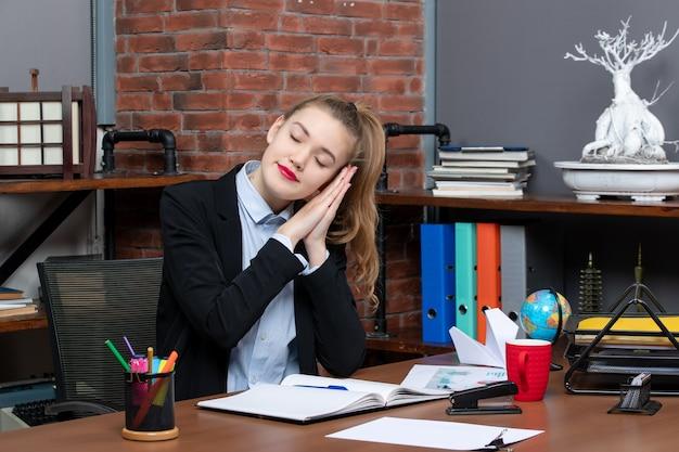 Bovenaanzicht van een jonge vrouw die aan een tafel zit en op kantoor slaapt