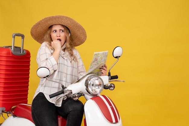 Bovenaanzicht van een jonge vrouw die een hoed draagt en op de motorfiets zit en de kaart vasthoudt, voelt zich verrast op geel