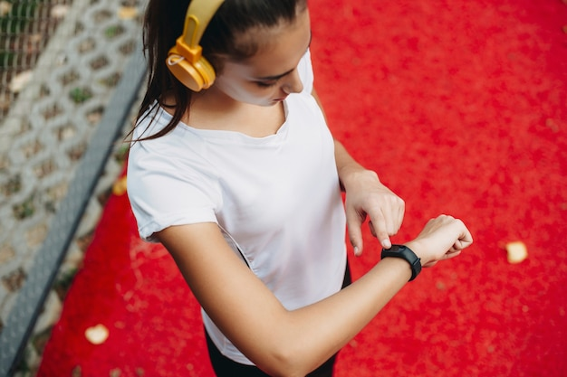 Bovenaanzicht van een jonge vrouw die haar sporthorloge bekijkt na het doen van cardio en het luisteren van muziek buiten in een sportpark.