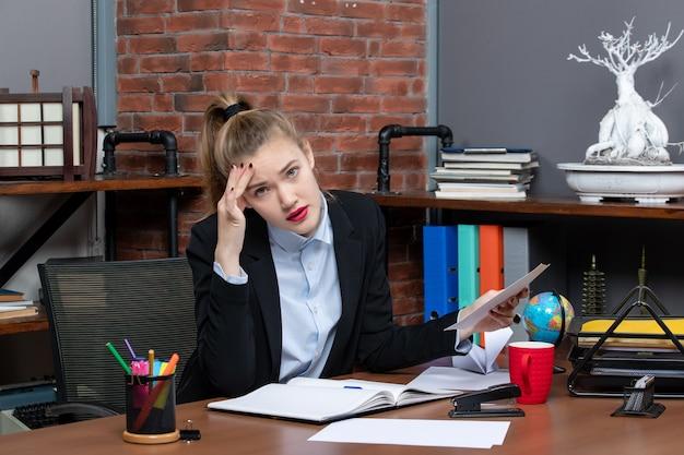Bovenaanzicht van een jonge vrouw in diepe gedachten die aan een tafel zit en een document op kantoor vasthoudt