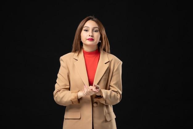Bovenaanzicht van een jonge vrouw in een lichtbruin pak die er ontevreden uitziet in het donker