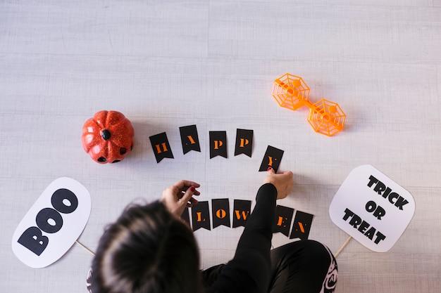 Bovenaanzicht van een jonge vrouw maakt halloween-slinger. creatieve diy. home decor project party. halloween ambachten inspiratie.