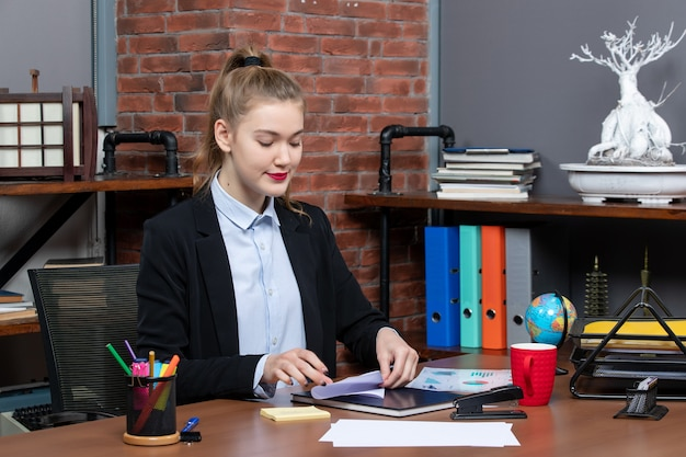 Bovenaanzicht van een jonge vrouwelijke kantoormedewerker die aan haar bureau zit en zich concentreert op het doen van haar werk
