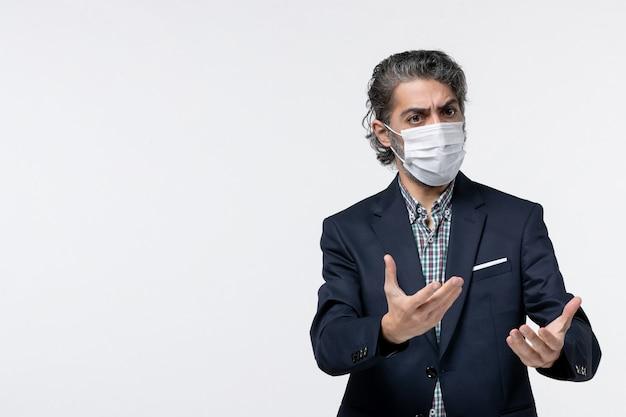 Bovenaanzicht van een jonge zakenman in pak met een masker en verward over iets op een witte ondergrond