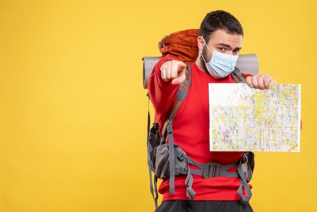 Bovenaanzicht van een jonge zelfverzekerde reiziger die een medisch masker draagt met een rugzak met een kaart die naar voren wijst op geel on