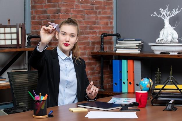 Bovenaanzicht van een jonge zelfverzekerde vrouwelijke kantoormedewerker die aan haar bureau zit en een papieren vliegtuigje speelt