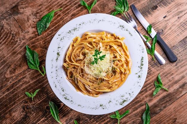 Bovenaanzicht van een kaasachtige pasta op een witte plaat