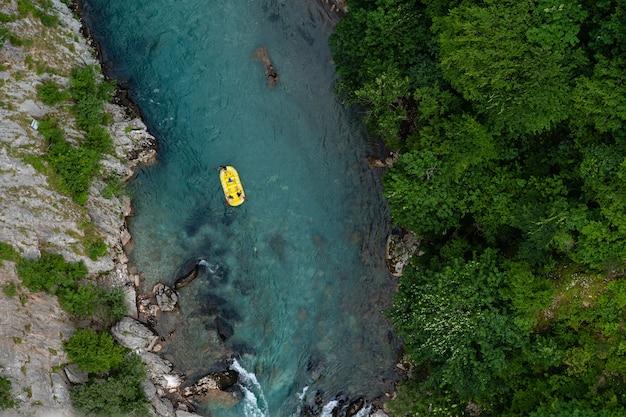 Bovenaanzicht van een kajak in een rivier die overdag in het bos is vastgelegd