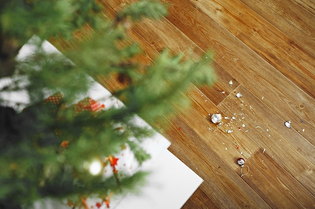 Bovenaanzicht van een kerstboom, slippers en gebroken kerstballen. het concept van mislukte voorbereiding op het nieuwe jaar. een gebroken rode glazen bol ligt op de houten vloer.
