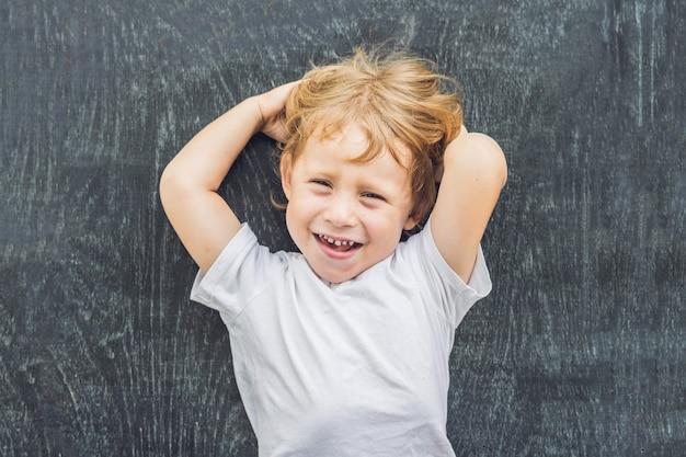 Bovenaanzicht van een kleine blonde jongen jongen met ruimte voor tekst en symbolen op de oude houten achtergrond
