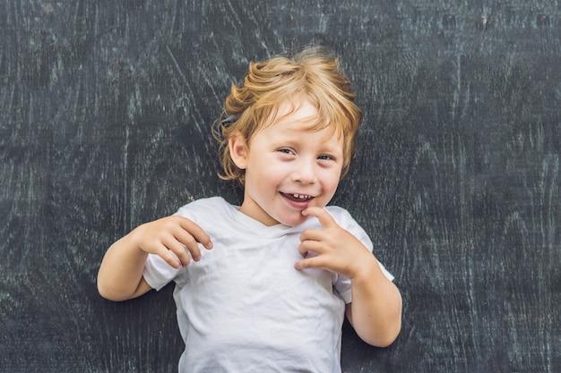 Bovenaanzicht van een kleine blonde jongen jongen met ruimte voor tekst en symbolen op de oude houten.
