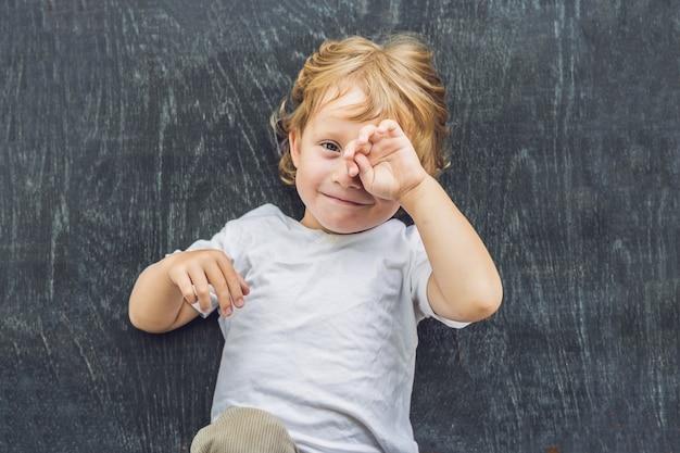 Bovenaanzicht van een kleine blonde jongen jongen met ruimte voor tekst en symbolen op het oude houten oppervlak