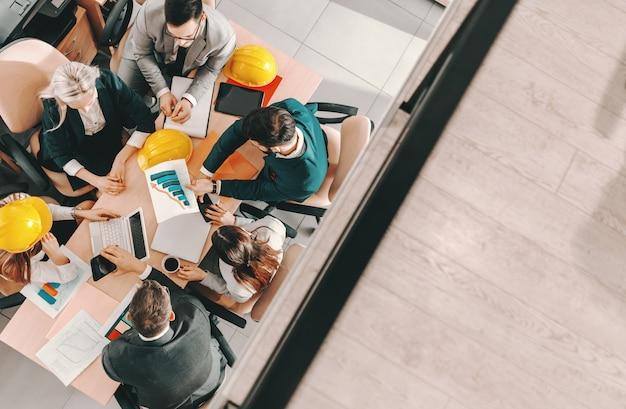 Bovenaanzicht van een kleine groep architecten in formele slijtage aan tafel zitten en project gedaan krijgen. als u zich op het probleem concentreert, ziet u geen oplossing.