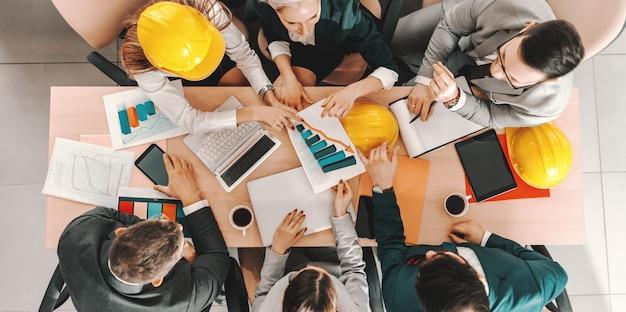 Bovenaanzicht van een kleine groep architecten in formele slijtage aan tafel zitten en project gedaan krijgen. wees niet dezelfde, wees beter.