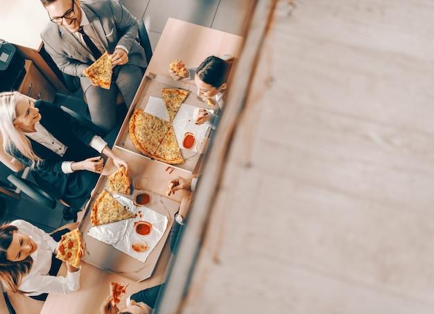 Bovenaanzicht van een kleine groep mensen uit het bedrijfsleven pizza eten voor de lunch. het leven is goed, jij maakt het goed.