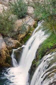 Bovenaanzicht van een kleine waterval op een rivier in de zomer.