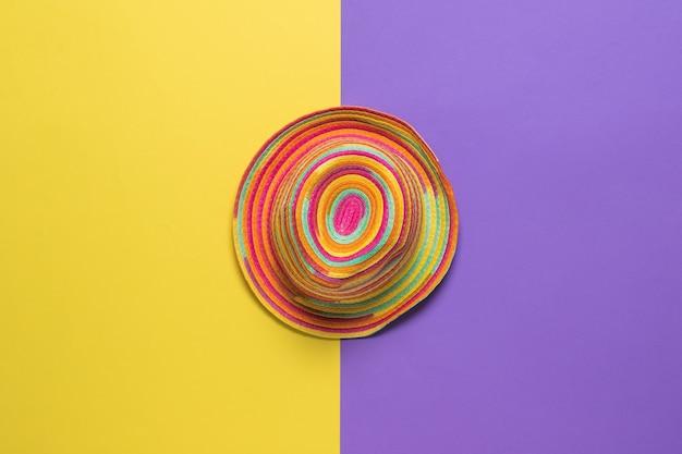 Bovenaanzicht van een kleurrijke zomerhoed op een geel en paars oppervlak