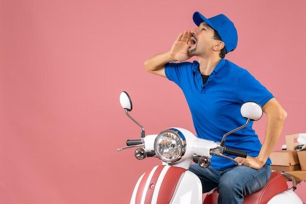 Bovenaanzicht van een koeriersman met een hoed die op een scooter zit en bestellingen aflevert die iemand belt op een pastelkleurige perzikachtergrond