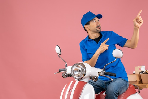 Bovenaanzicht van een koeriersman met een hoed die op een scooter zit en bestellingen aflevert die naar boven wijzen op een pastelkleurige perzikachtergrond
