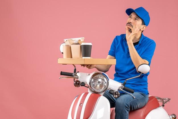 Bovenaanzicht van een koeriersman met een hoed die op een scooter zit en diep nadenkt over een pastelkleurige perzikachtergrond
