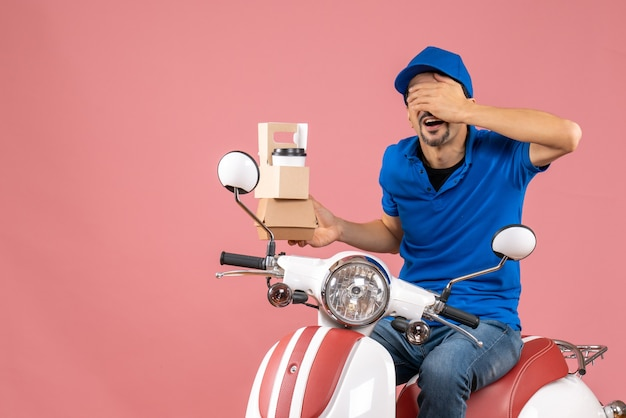 Bovenaanzicht van een koeriersman met een hoed die op een scooter zit en orders toont die zijn ogen sluiten op een pastelkleurige perzikachtergrond