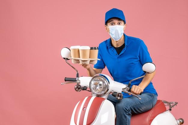 Bovenaanzicht van een koeriersman met een masker met een hoed die op een scooter zit en bestellingen op een pastelkleurige perzikachtergrond toont