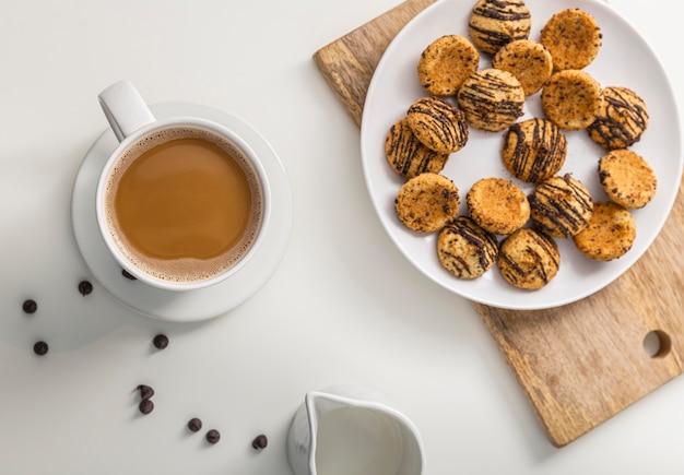 Bovenaanzicht van een koffiekopje met plaat van koekjes