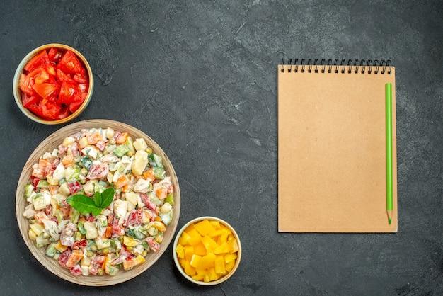 Bovenaanzicht van een kom groentesalade aan de linkerkant met schalen met groenten en een notitieblok aan de zijkant op een donkergrijze achtergrond