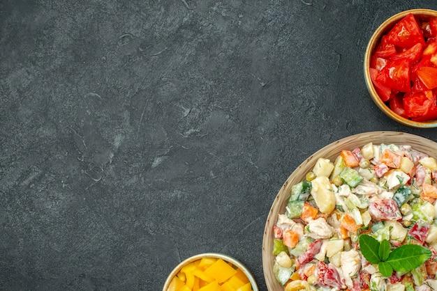 Bovenaanzicht van een kom met groentesalade aan de rechterkant met schalen met groenten aan de zijkant op een donkergrijze achtergrond