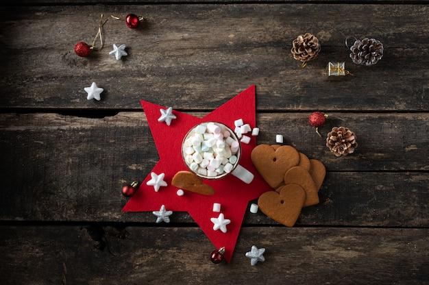 Bovenaanzicht van een kop warme chocolademelk met zoete marshmallows geplaatst op een rode vakantiester met koekjes en kerstversiering eromheen.