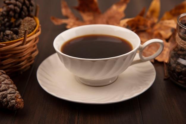 Bovenaanzicht van een kopje gearomatiseerde koffie met goudgele bladeren en dennenappels geïsoleerd op een houten oppervlak