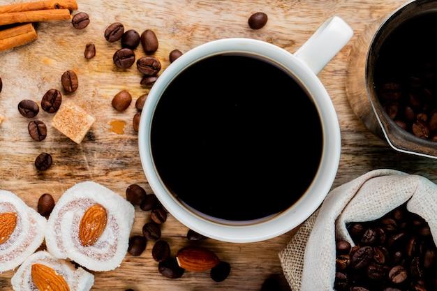 Bovenaanzicht van een kopje koffie en turkse lekkernijen rahat lokum op een rustieke achtergrond