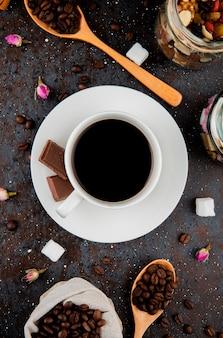 Bovenaanzicht van een kopje koffie met chocolade en een houten lepel met koffiebonen op zwarte achtergrond