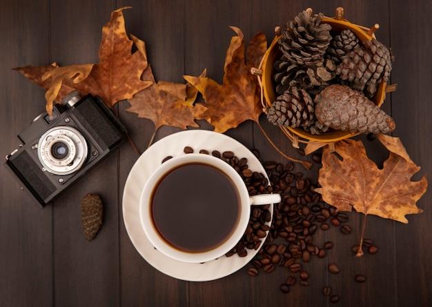 Bovenaanzicht van een kopje koffie met dennenappels op een emmer met goudgele bladeren en koffiebonen geïsoleerd op een houten muur