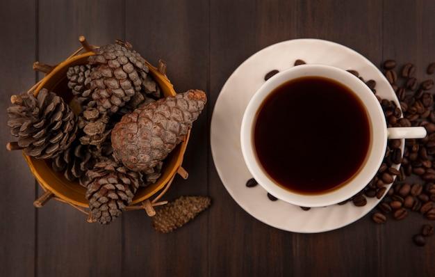 Bovenaanzicht van een kopje koffie met dennenappels op een emmer met koffiebonen geïsoleerd op een houten oppervlak
