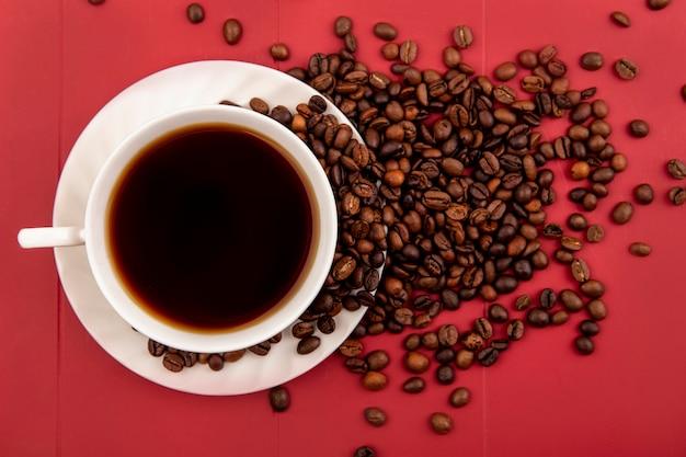 Bovenaanzicht van een kopje koffie met koffiebonen geïsoleerd op een achtergrond van onderzoek
