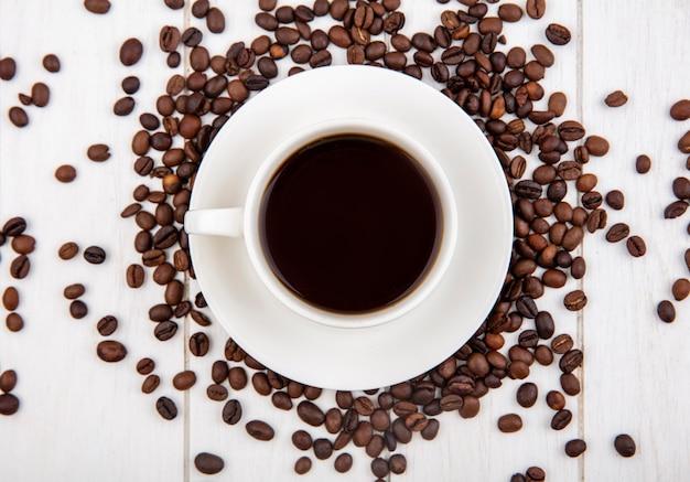 Bovenaanzicht van een kopje koffie met koffiebonen geïsoleerd op een witte houten achtergrond